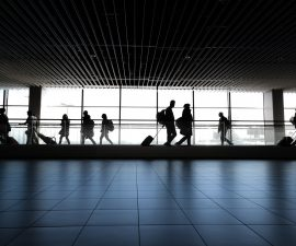 Dans un aéroport, des voyageurs circulent avec leurs bagages.