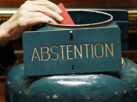 Une main qui vote dans une urne nommée abstention