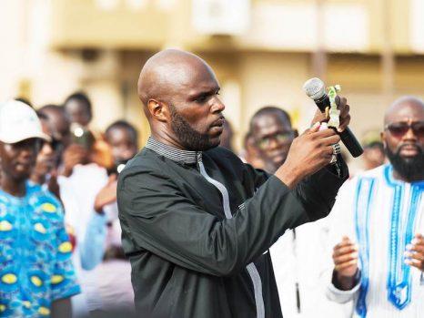 Kemi Seba brûle un billet Franc CFA devant un public, en Afrique